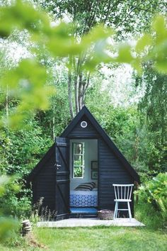 black painted scandinavian summerhouse in the woods