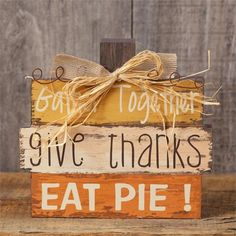 NEW!  Great new wooden fall sign.  Shaped like a pumpkin and accented with a raffia bow and wire curley-Qs.  It reads Gather Together, Give Thanks, Eat Pie.  It measures 8 tall by 7 across.