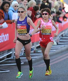 Jessica Augusto of Portugal (L) and Remi Nakazato of Japan run during the Virgin London Marathon 2013 on April 21, 2013 in London, England.