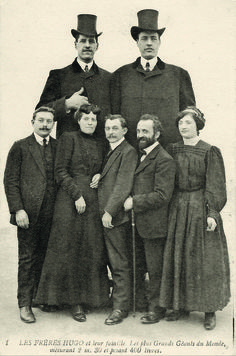 Brothers Baptiste (7'6'', 1887-1914) and Antoine Hugo (7'5'', 1876-1916) both had gigantism from pituitary tumors.  They are shown here with their family.
