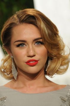 Classic beauty look. Love the big short hair. Red lips with a touch of orange.