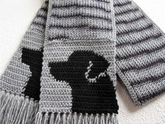 Handmade, Labrador Retriever scarf. Scarf features a black Labrador Retriever silhouette on each end. The scarf colors range from light silver to black. We loom knit the length of the scarf using a striping gray and black yarn. The length is double thick and then I crochet the sides of the scarf and the Labrador retrievers into the ends. The labs are part of the scarf and not added as an applique. All loose ends are sewn in and the last photograph shows the back of the scarf.  Scarf measures…