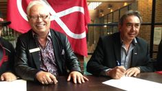 The mayor of the Municipality of Greenstone, Renald Beaulieu (l) and the president of the Metis Nation of Ontario, Gary Lipinski (r) smile as they sign the historic General Relationship Agreement in front of the Metis flag, in Thunder Bay.