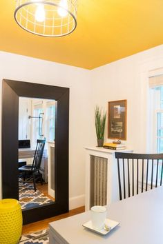 A tall black framed mirror visually expands this small home office. The eye-catching yellow ceiling with a cage light fixture is balanced with crisp white walls to really make it pop. Yellow Ceiling, Colored Ceiling, Yellow Walls, White Walls, Bedroom Wall Colors, Room Colors, Paint Colors, Interior Decorating, Interior Design