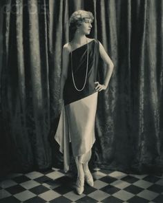 c. 1924. Actress Marion Morehouse (also known as Mrs. e. e. Cummings) is wearing a one-shouldered bias-cut silk satin sheath gown with dark, diagonally cut drop bodice and light-colored slim skirt wrapped to form two-layered hemline, matching scarf falling from one hip, designed by Callot; pearl earrings, necklace, bracelets, rings; and satin, twisted T-strap shoes.