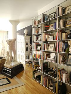 Stainless shelving by USM is filled with a mix of classical sculptures, framed photos and art books. The largest classical sculpture is nick...