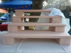 """DIY foam risers for craft booths """"i made these modular shelves resting on blocks out of foam core cut up and stitched into covers of cotton knit. they are so light and yet so sturdy. we love foam core! Craft Stall Display, Craft Booth Displays, Display Shelves, Display Ideas, Booth Ideas, Craft Booths, Soap Display, Craft Font, Vendor Displays"""