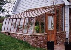 This lean-to greenhouse has a brick base for thermal mass and is partially buried for insulation. Attachment to the house also helps with insulation.
