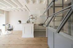 大阪府茨木市、築43年の中古分譲マンションをリノベーション。白を基調とし躯体の形状を生かしたスケルトン天井が印象的な空間は、ドアを開けばまるで海外映画に登場するアパルトマンのよう。冷蔵庫などの家電を間仕切りで隠し生活感を出さない工夫や、細いフレームがスタイリッシュなアイアンの建具など、デザイン関係のお仕事をされているご夫婦のこだわりとセンスが光る特別な空間となりました。