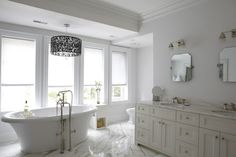 Amazing master bathroom with iron lace drum chandelier over a Kohler freestanding tub with satin floor-mount tub filler, over marble tiled floor. Features; a cream double vanity with white marble countertops, clipped cornered pivot mirrors and Restoration Hardware Dillon Double Sconces.