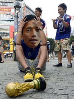A Japanese football fan wears a Yuto Nagatomo mask while sitting on a street corner in Tokyo after Japan were knocked out of the World Cup by Colombia