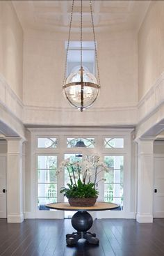 large two story entry with round table and painted architectural woodwork