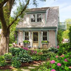 Cedar shingles cured by the salt air, window brackets borrowed from the 1880s main house, a sunny balcony, and a shady elm give the former garage a storybook look.The entry lights and cast-iron front step are salvaged finds.: