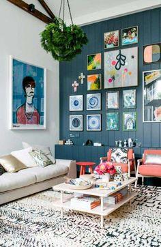 déco petit salon - lambris mural bois peint bleu, fauteuils de couleur mandarine, canapé blanc et tapis blanc à motifs noirs