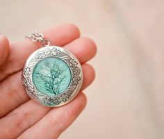 This 30 inch antique silver chain necklace features a 32 mm photo locket that can hold two 24mm (roughly 1 inch) photos. The locket is adorned with a beautiful high quality tree silhouette print seale