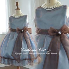 「色の魔術」 このドレスを見たときに、思い浮かぶ言葉です。 何気ないドレスなのに、上品で洗練された雰囲気がある理由は、ドレスのパターン(キャサリンコテージのデザイナーが起こした型紙)の美しさと「色の魔術」 異素材の生地で、光沢のある水色とブラウンを重ねたことで生みだされたブルーグレーの微妙な色合い。 このドレスは、光りのあたり具合や着ている人の所作に合わせて絶妙のグラデーションを醸し出します。 ゆったりしたスカート、表地にかぶせているオーガンディー、たっぷりとして、長く垂らした袋縫いの前リボンに、後ろのリボン。