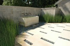 Modern courtyard garden with limestone & river pebble paving by Howard Design Studio.