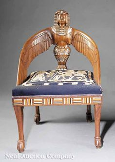 An Egyptian Revival Carved and Inlaid Hardwood Figural Armchair, early 20th c., the back a male figure, curved winged arms, original appliqué upholstery, straight seat rail, the legs ending in hoof feet.