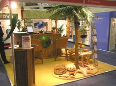 Birmingham NEC | Themed exhibition stand - palm tree, macaws, Caribbean beach bar, Caribbean pod, bar stools, bamboo furniture, themed table centre, lobster pots, giant clam, giant starfish, lobster, driftwood and fishing net by www.stressfreehire.com #venuetransformers