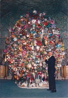 Walter Dymond, groundskeeper of Harold Lloyd's estate, Greenacres, with the Lloyd Christmas tree.  He was responsible for the construction of the Christmas tree from two trees (wiring the branches of one into the other), and placed the ornaments where Mr Lloyd directed.  The tree remained up, all year 'round. - (1972)
