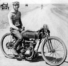 Early Harley racer doing a photo ops.  You must really have a firm grip on to those handlebars to keep your hands from sliding off.