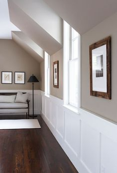Wall color, white board and batten, beautiful dark wood flooring with matching picture frames, and gable windows