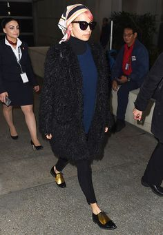 Nicole Richie wearing wearing a bold and colorful scarf tied apron-style with a black turtleneck, black fuzzy coat, and black pants with oxfords with gold panel