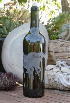 Tandem Horses Design is carved / sandblasted onto empty wine bottles that transform into oil lamps.