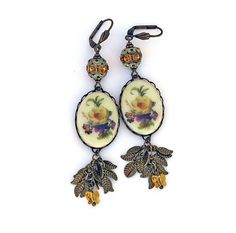 Vintage Limoges long earrings, Victorian/Shabby Chic genres, with a beautiful, vintage floral cabochon of yellow, purple, green, and gold on a creamy porcelain background, vintage Swarovski citrine crystal rondelles and crystal butterflies, and delicate brass leaf chain. The shell motif, leverback earwires are brass.  Length: 2-3/4 inches (7 cm), from the bottom of the earwire Width of cabochon: 3/4 inch (2 cm)