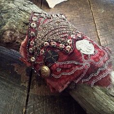 A tattered red, dusky pink and gold embroidered textile cuff, primitively hand stitched and pieced together using recycled fabric and found elements:  the fabric from the costume of an old Balinese hand puppet, vintage sari scraps, antique kuchi, brass buttons and a salvaged coat hook. I start with  an empty strip of backing fabric and build layer by layer,  so that a collection of scraps and remnants become a story stitched  together into a cohesive hole.  Around 8 inches (20 cm) including…