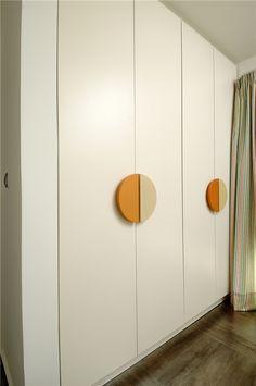Τετράφυλλη ντουλάπα με πόρτες από λευκή λάκα με ημικυκλικά πόμολα επίσης λακαριστά.