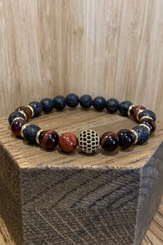 Beautiful gold coloured metal intermingled with smouldering black lava and red tiger's eye beads. This hot and fiery piece of wrist jewellery is styling yet oh so practical! The elastic band that runs through the beads stretches over your hand easily Wire Jewelry, Gemstone Jewelry, Beaded Jewelry, Jewelery, Handmade Bracelets, Bracelets For Men, Jewelry Bracelets, Lava Bracelet, Bracelet Cuir