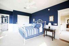 des murs en bleu foncé et un linge de lit bleu et blanc dans la chambre à coucher blanche