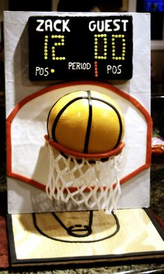 Basketball Cake - The score board is rice krispy treats covered in black fondant with fondant, royal icing and modeling chocolate for letters and numbers. Secured to the vertical cake board with white chocolate.  Backboard is white fondant trimmed in red fondant.  The basketball is chocolate cake covered in dyed burnt orange fondant with black fondant for the stripes.  Net is white fondant, need to work on this technique...the net lasted exactly two minutes after this photo was taken befo…