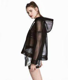 Schwarz. Oversize-Shirt aus festem, durchbrochenem Mesh. Das Shirt hat eine Kapuze mit Kordelzug, stark überschnittene Schultern und Bündchen an Ärmeln und