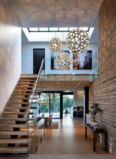 """"""" Todo me gusta, las lamparas son lo mejor; y con ese muro y ventanales al fondo, la mezcla de materiales """"Dining area past the staircase.. Stunning foyer"""