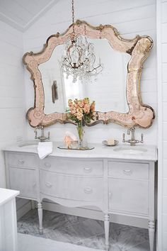I'm not normally one for pink, but this whitish gray bathroom vanity sink area with that huge ornate pink mirror and crystal chandy looks AMAZING!!