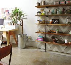 Pipe shelving with painted chevron background in living room