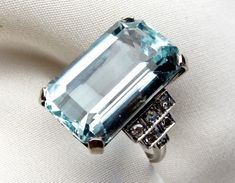 Mid 20th Century Aquamarine Cocktail Ring | Isadora's. Circa 1950. This elegant platinum and 14KT white gold cocktail ring is centered by a stunning 16.57 carat aquamarine stone. The shoulders of this wonderful ring are bead set with six single cut diamonds in a step style triangular pattern. The diamonds have a .35 carat total diamond weight, SI2 clarity and J color. $13,930