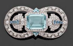 CARTIER Importante broche Art Déco en platine, en boucles ouvertes ajourées d'une frise géométrique sertie de diamants. Elle est centrée d'une aigue-marine et de diamants épaulée de deux pavages de diamants agrémentés d'aigue-marines calibrées disposées en gradins. Vers 1925.