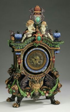 """Renaissance Revival majolica mantel clock by Hugo Lonitz with a movement by Japy Frres, having a flaming urn finial flanked by griffons and putti, above an arched crest with finials, centering a brass dial having Roman numerals framed with an acanthus molding, above a horned pan mask, rising on monopodial winged griffin supports with hairy paw feet connected by fruited swags, majolica case is unmarked, the movement is marked Japy Frres, 24.5""""h x 12.5""""w x 7.75""""d."""
