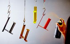 Several IKEA GRUNDTAL toilet roll holders are hung from the ceiling, each being spray painted in a different color.