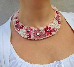Um romântico colar de crochê de fios de algodão em tons de rosa velho com inserções em strass e fecho botão.
