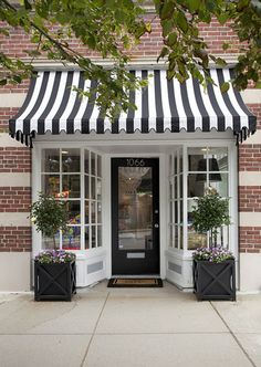 inspiration for awnings over the garage doors for garage conversion - black and white awning with boxwood planters