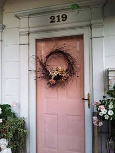 pink front door with a wreath created with mostly branches and a few small blooms