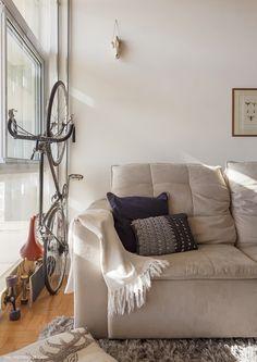 Sala de estar compacta tem sofá e tapetes claros,
