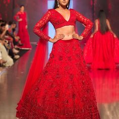 #KALKIxZinnia: The Royal Fantasy. A glimmering sea of 3D summer florals and feather light sheer sleeve capes will mark this fiery red hand embroidered lehenga, adjuring up the image of mythical summer paradise in your minds. Contrasting exemplary modern tailoring against traditional silhouette, the lehenga is equated with plunging deep V cut bustier that looks like a refined representation of a contemporary aesthetic as a whole.