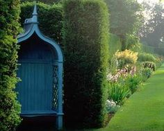 Painted arbour with seat in hedge alcove at Hazlebury Manor, Wiltshire, UK.