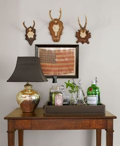 The American flag in this home's entryway is a find from the Brimfield Antique Show; the vintage mercury-glass lamp and hunting trophies add to the collected look of the minibar area. Brimfield Antique Show, Mercury Glass Lamp, Vintage Flag, New York Homes, Most Beautiful Gardens, 4th Of July Decorations, Hallway Decorating, Decorating Ideas, American Flag