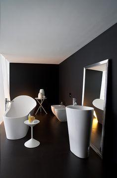 baño de diseño con sanitarios de color blanco, bañera exenta lavabo de pie, espejo hasta el suelo, techo color blanco, paredes y suelo color negro